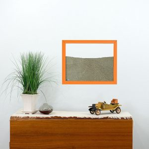 orange painted wood frame ant farm hanging on wall