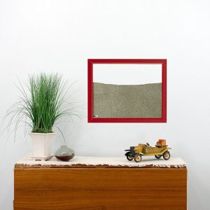 red painted wood frame ant farm hanging on wall